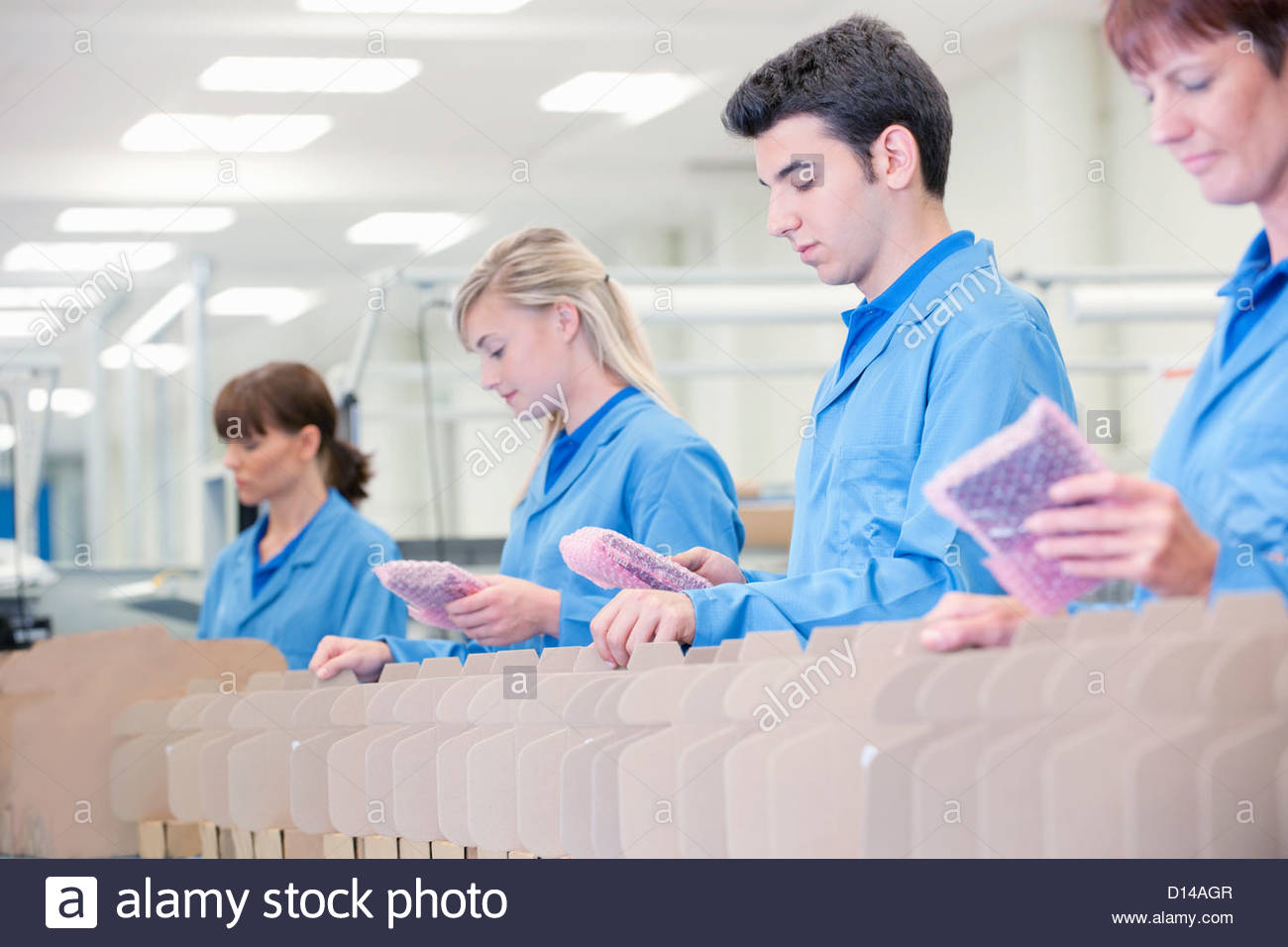Workers packing products in manufacturing plant - Stock Image