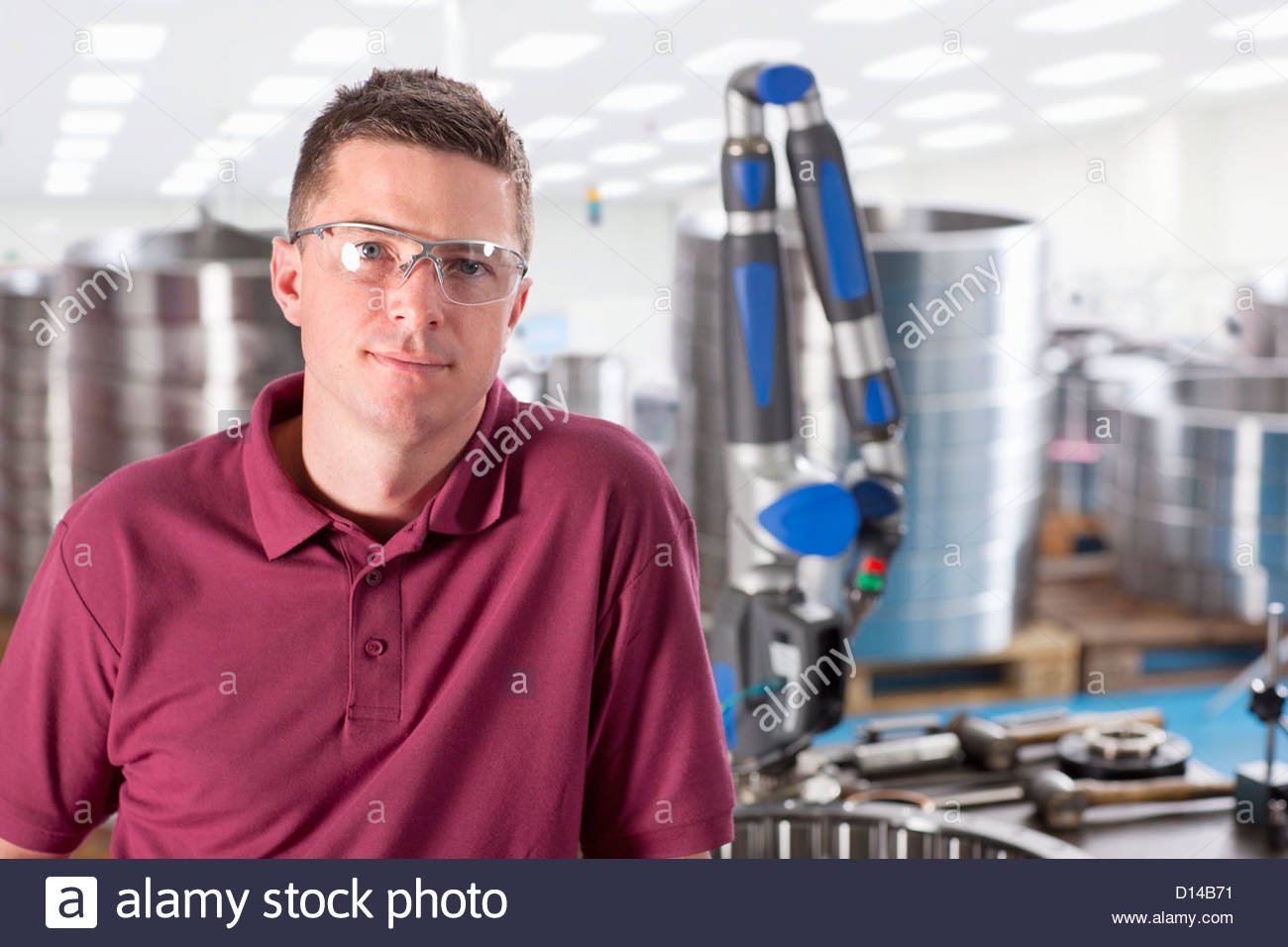 Portrait of smiling technician in steel bearing manufacturing plant - Stock Image