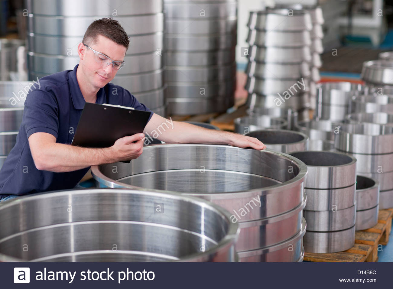 Technician checking steel roller bearing inventory in warehouse - Stock Image