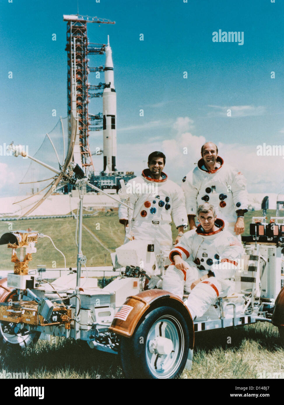 Apollo 17 crew photographed with a Lunar Roving vehicle and Saturn V rocket. They are Eugene A Cernan (seated), - Stock Image