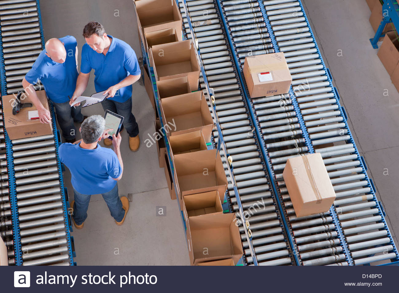Workers meeting among boxes on conveyor belts in distribution warehouse Stock Photo