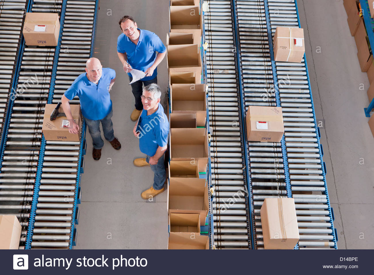 Portrait of smiling workers among boxes on conveyor belts in distribution warehouse - Stock Image