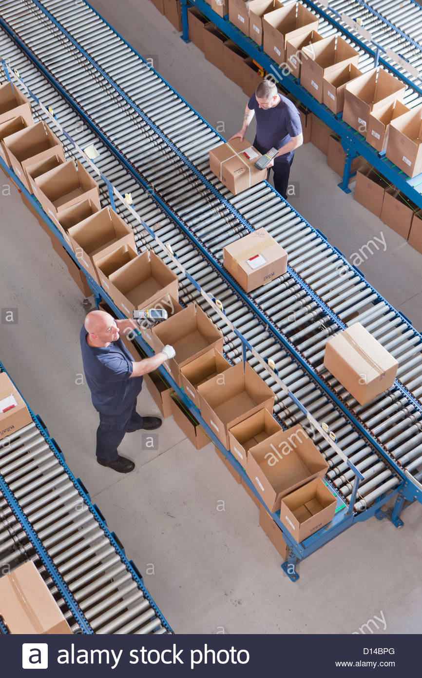 Workers packing boxes on conveyor belts in distribution warehouse - Stock Image