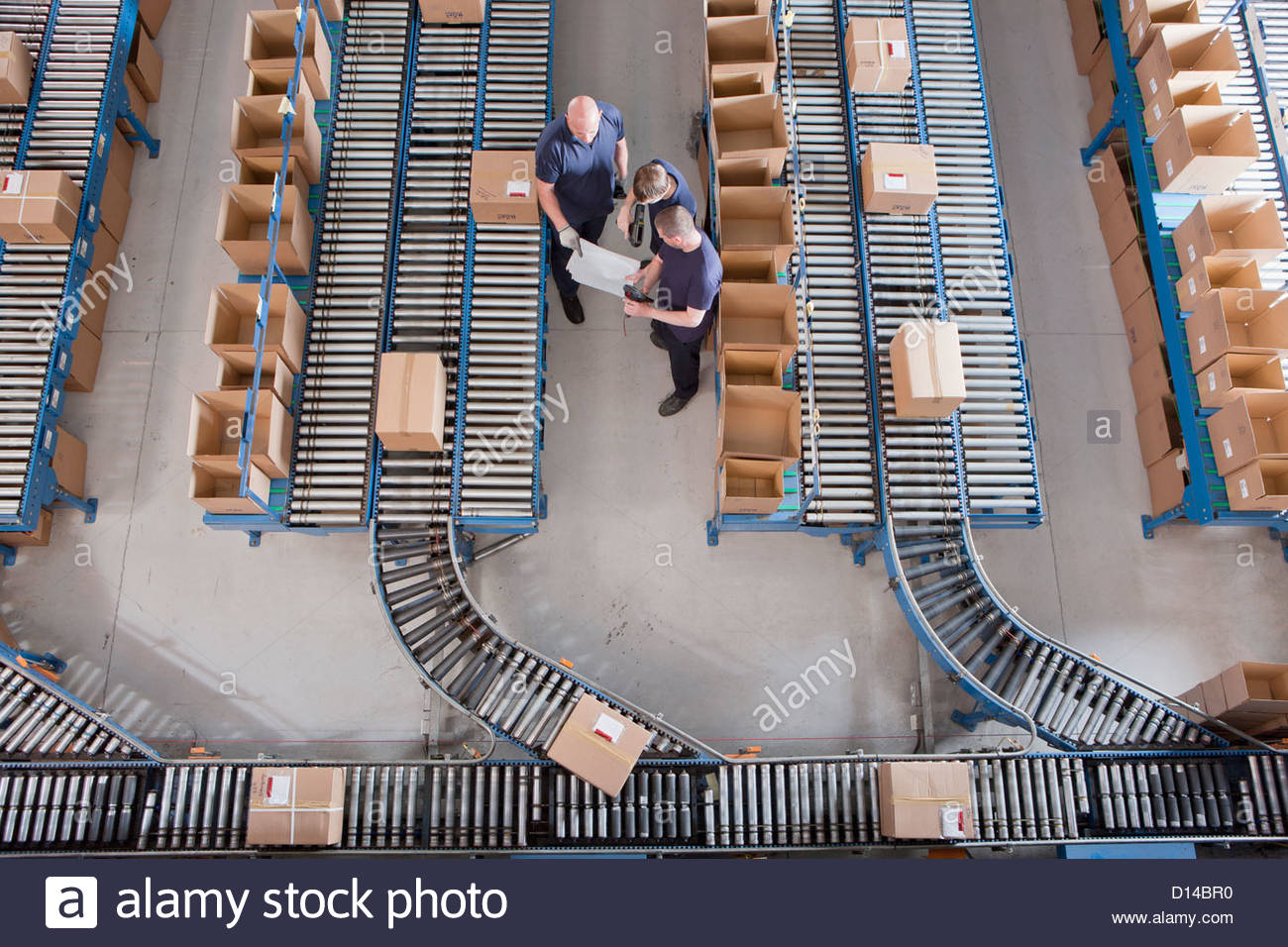 Workers meeting among boxes on conveyor belts in distribution warehouse - Stock Image