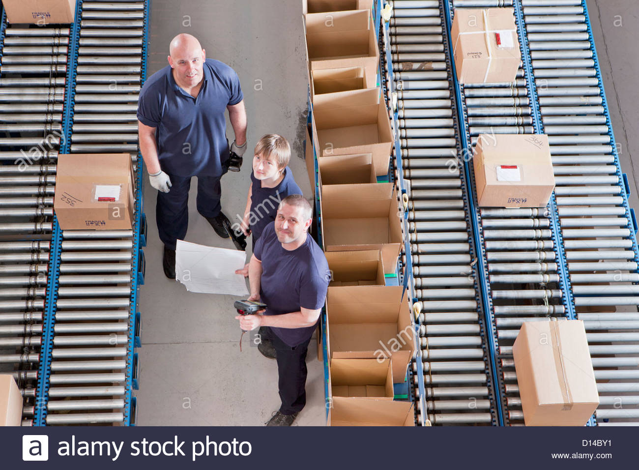 Portrait of workers packing boxes on conveyor belts in distribution warehouse - Stock Image