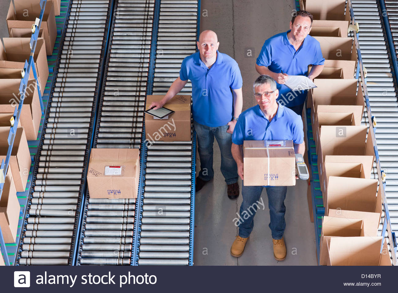 Portrait of smiling workers packing boxes on conveyor belts in distribution warehouse - Stock Image