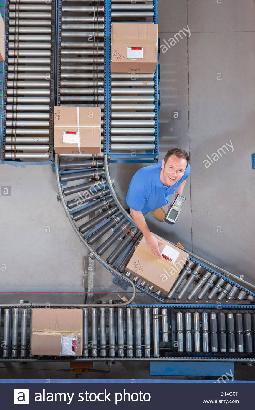 Portrait of smiling worker with bar code reader scanning box on conveyor belt in distribution warehouse - Stock Image