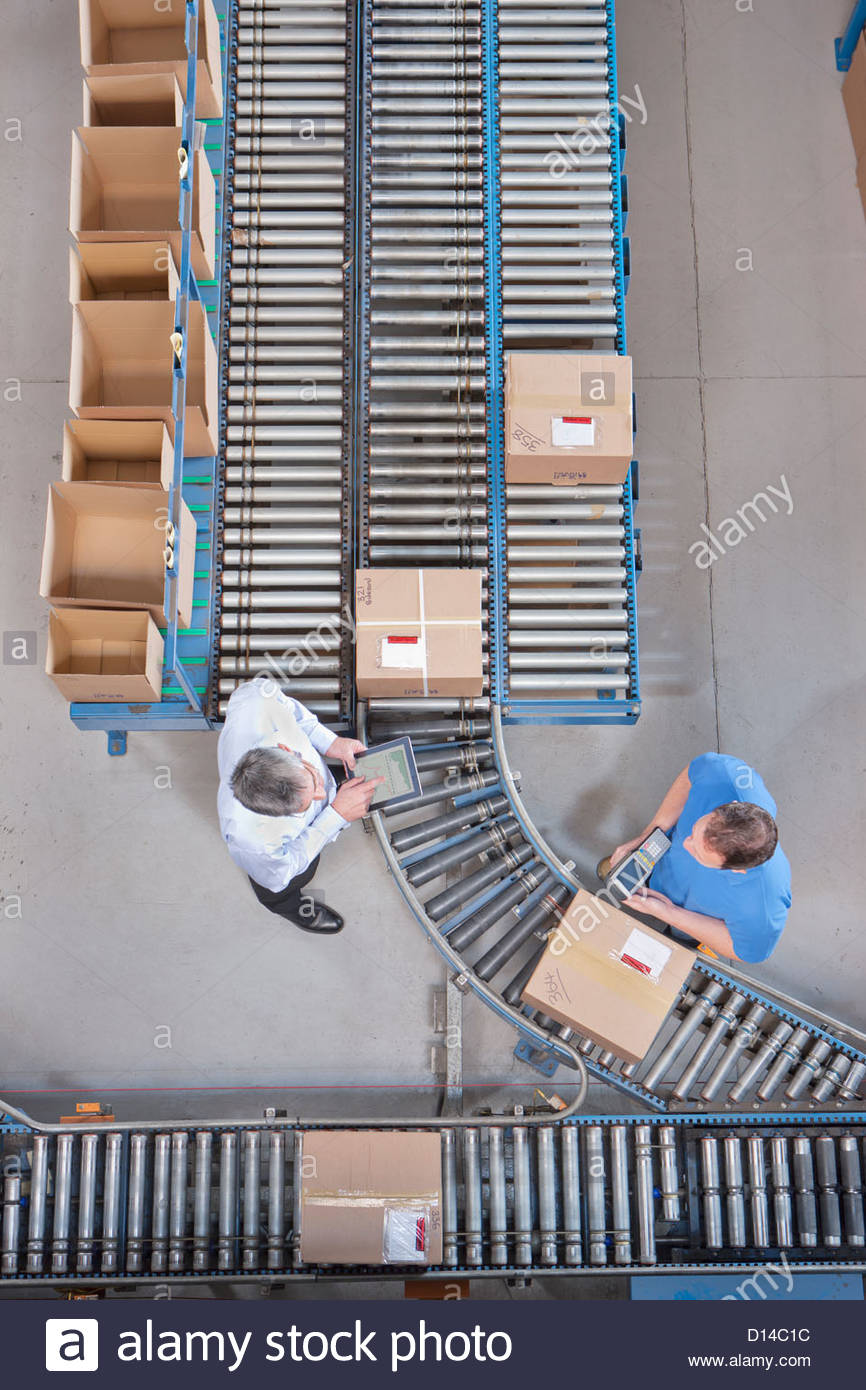 Businessman with digital tablet and worker packing box at conveyor belt in distribution warehouse - Stock Image