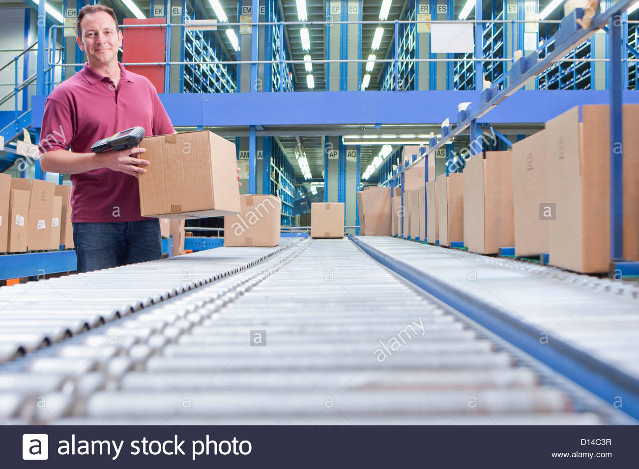 Portrait of smiling worker with bar code reader and box at conveyor belt in distribution warehouse - Stock Image
