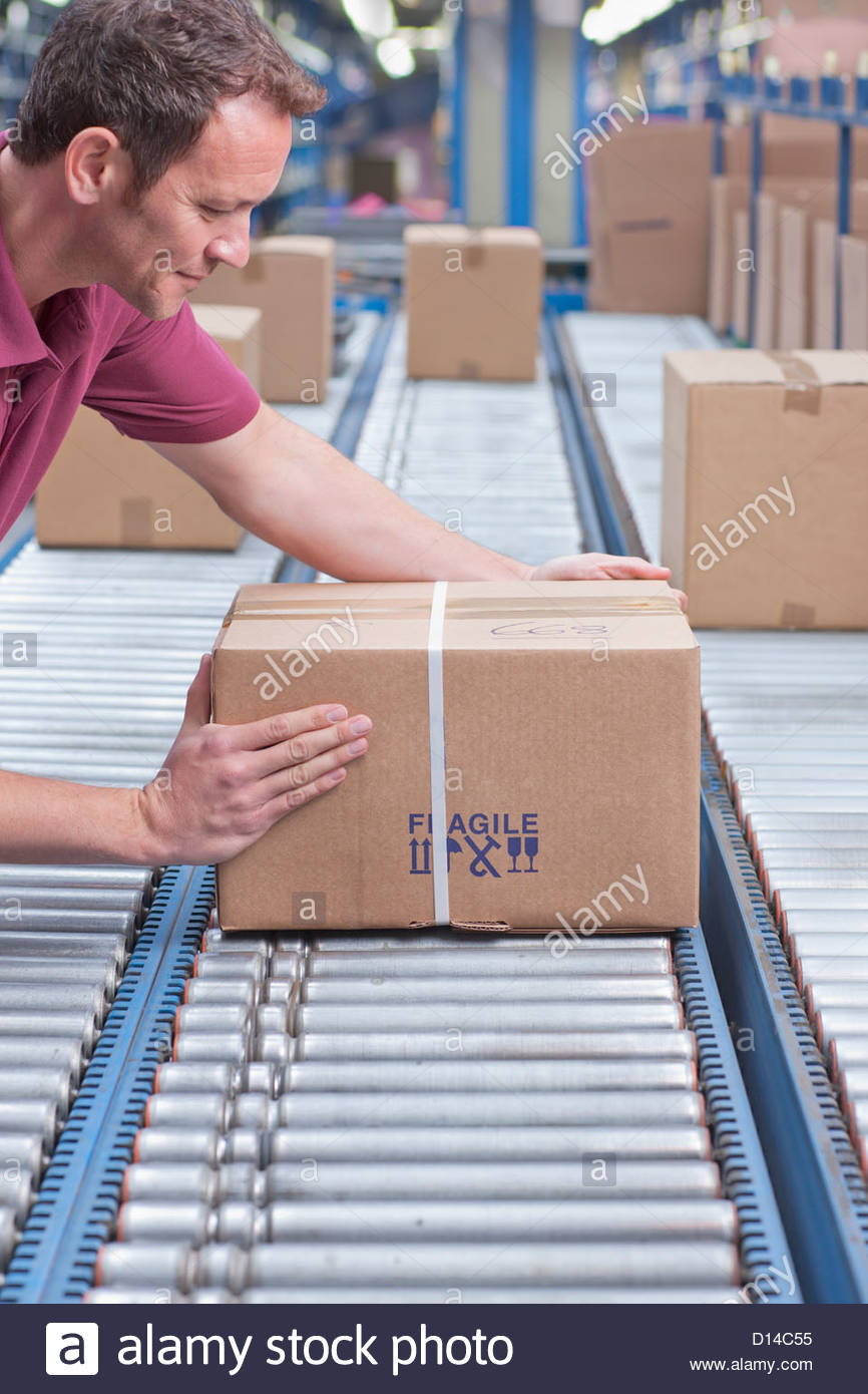 Worker packing box on conveyor belt in distribution warehouse - Stock Image