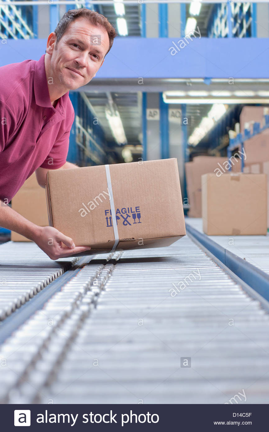 Portrait of smiling man packing box on conveyor belt in distribution warehouse - Stock Image