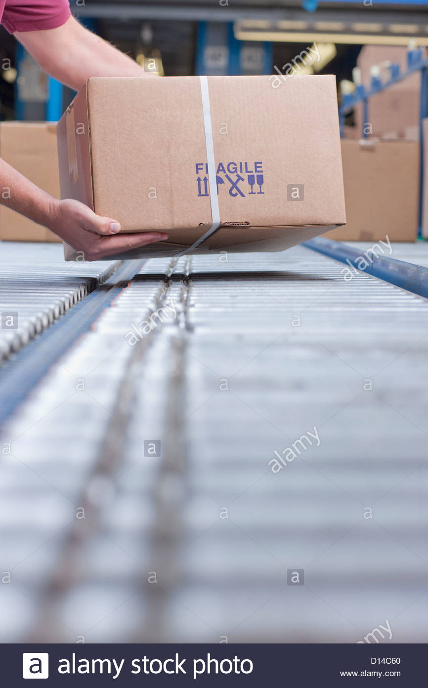 Hands of worker packing box on conveyor belt in distribution warehouse - Stock Image