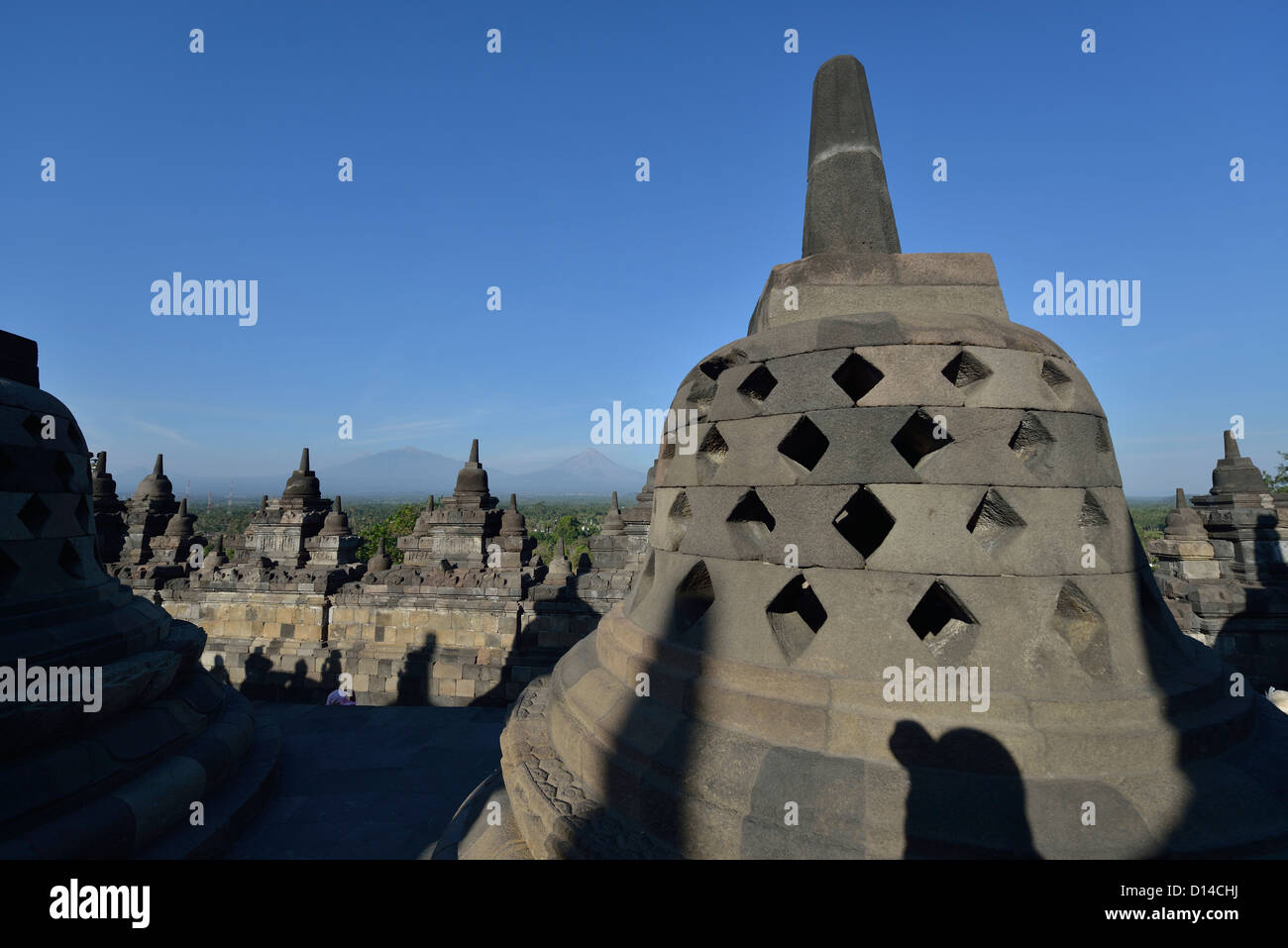 The stoupas at Borobudur with the view of Merapi in the background; Central Java, Indonesia. - Stock Image