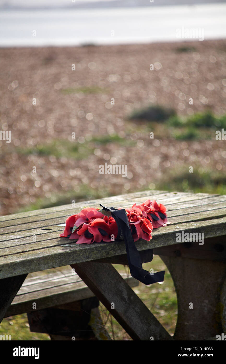 Poppy wreath on table at Calshot beach, Hampshire, England UK  in November - Stock Image