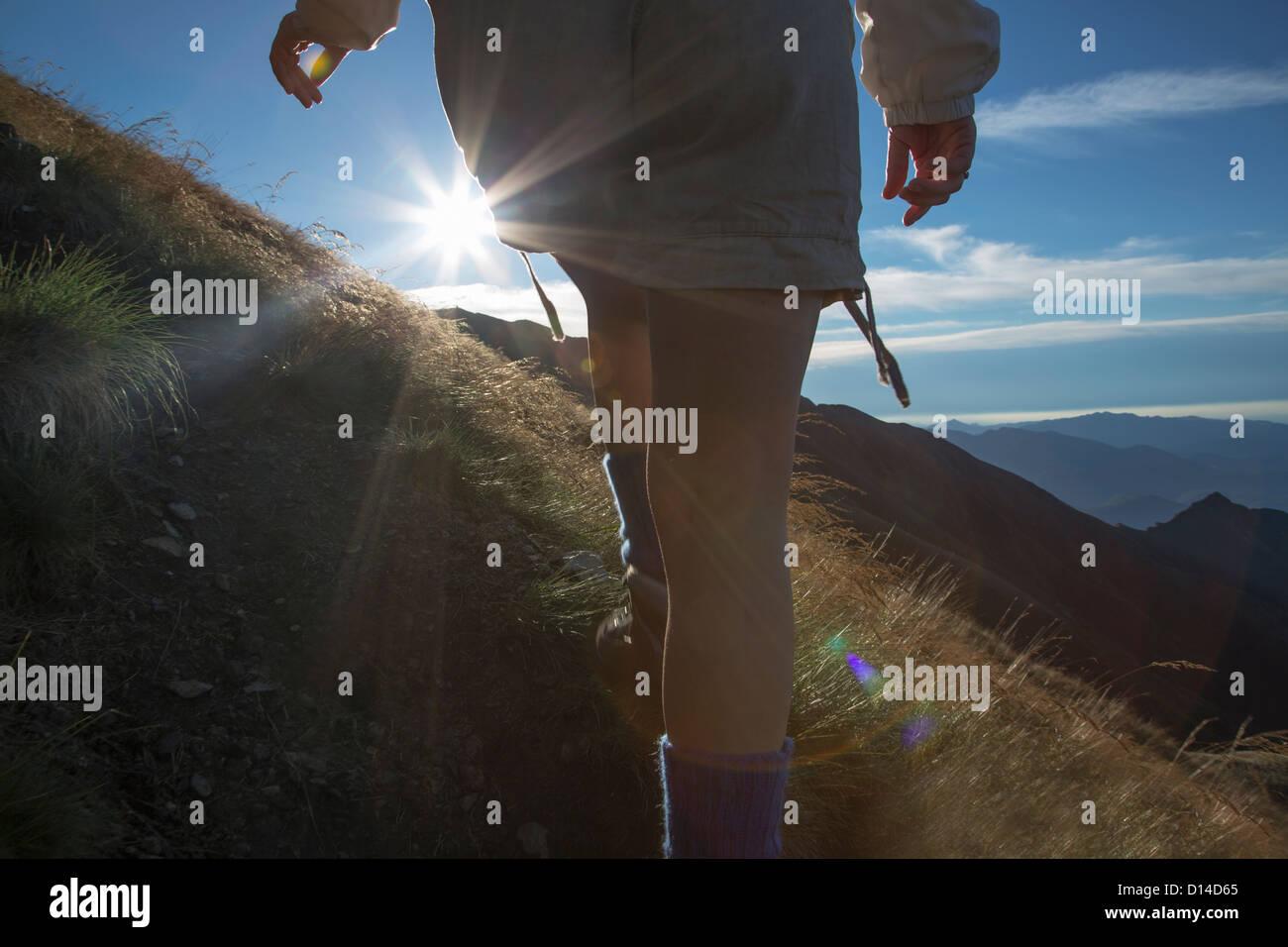 Woman hiking on rural hillside Stock Photo