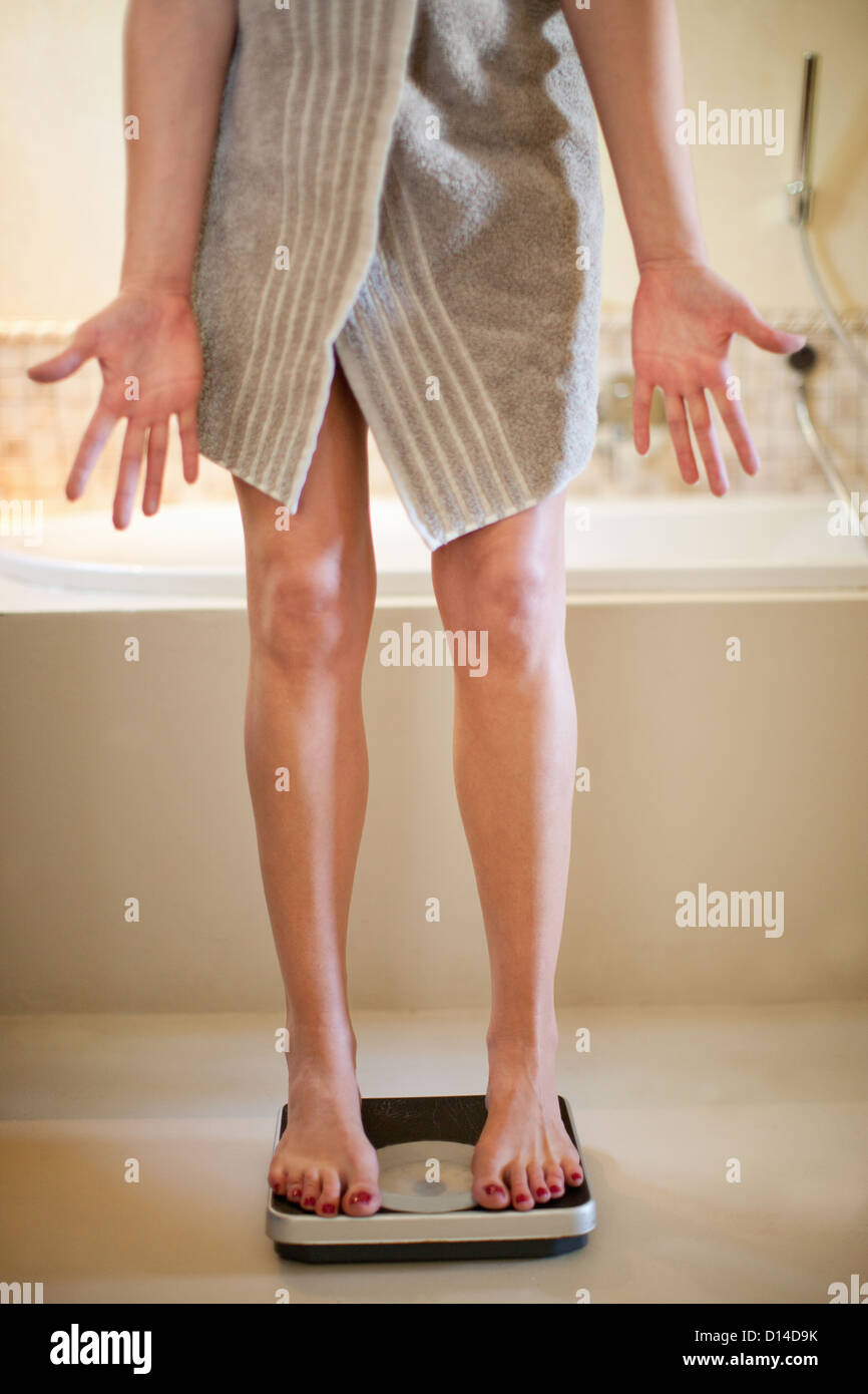 Woman weighing herself on scale - Stock Image