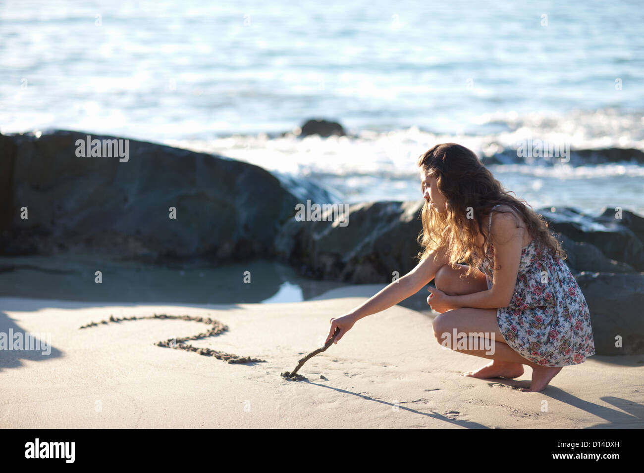 Woman drawing question mark in sand - Stock Image