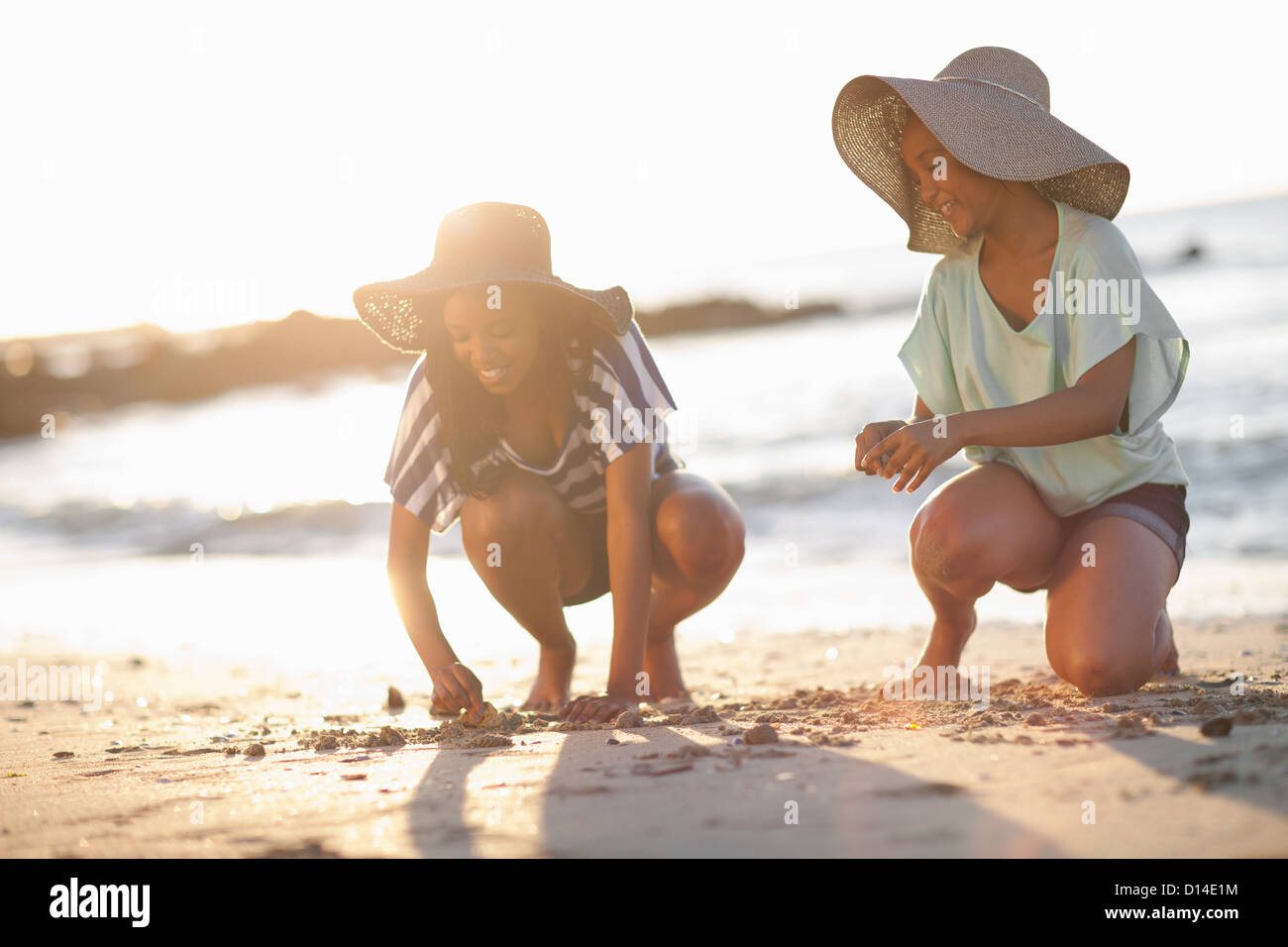 Women drawing in sand on beach - Stock Image