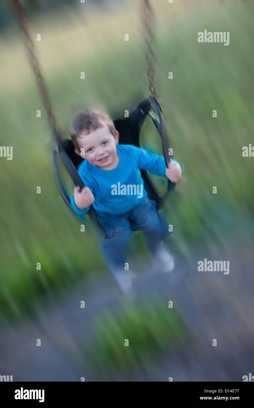 Blurred view of boy swinging - Stock Image