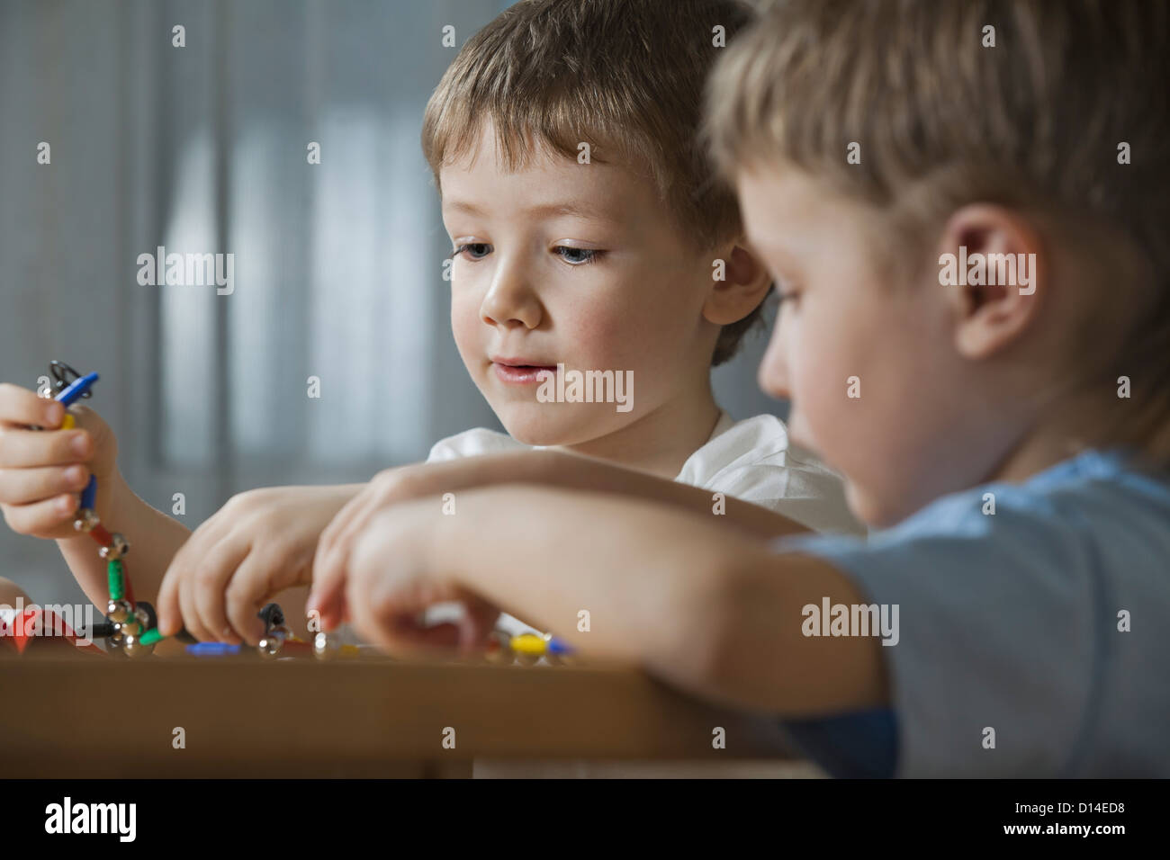 young boys playing with shape game Stock Photo