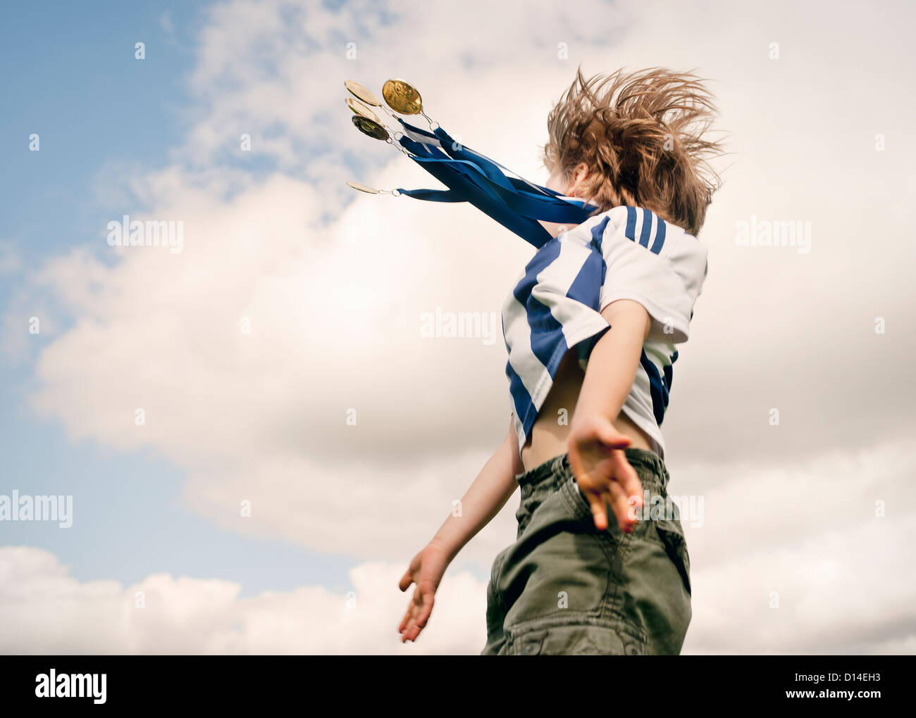 Boy with medals cheering outdoors - Stock Image