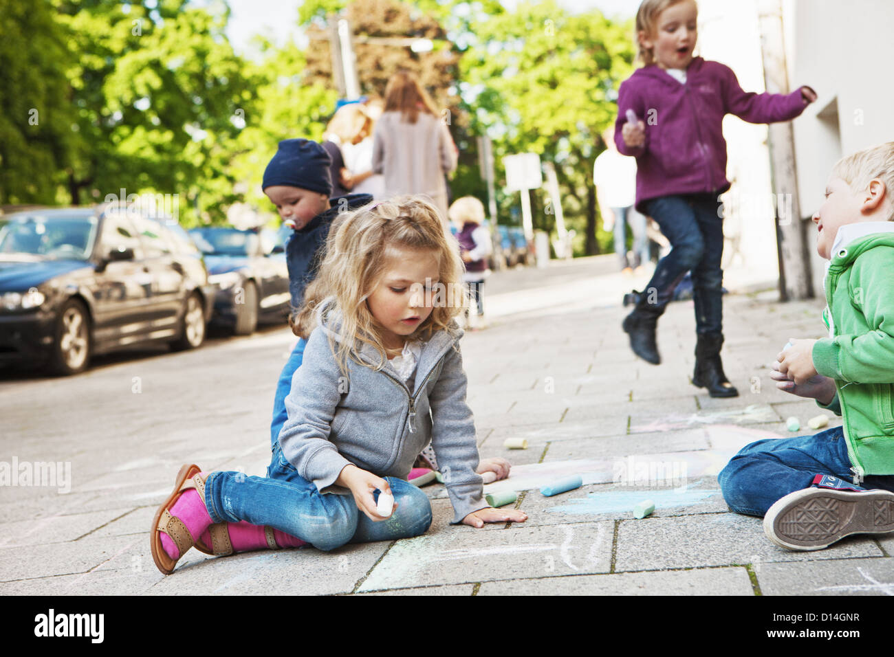 Children drawing on sidewalk with chalk - Stock Image