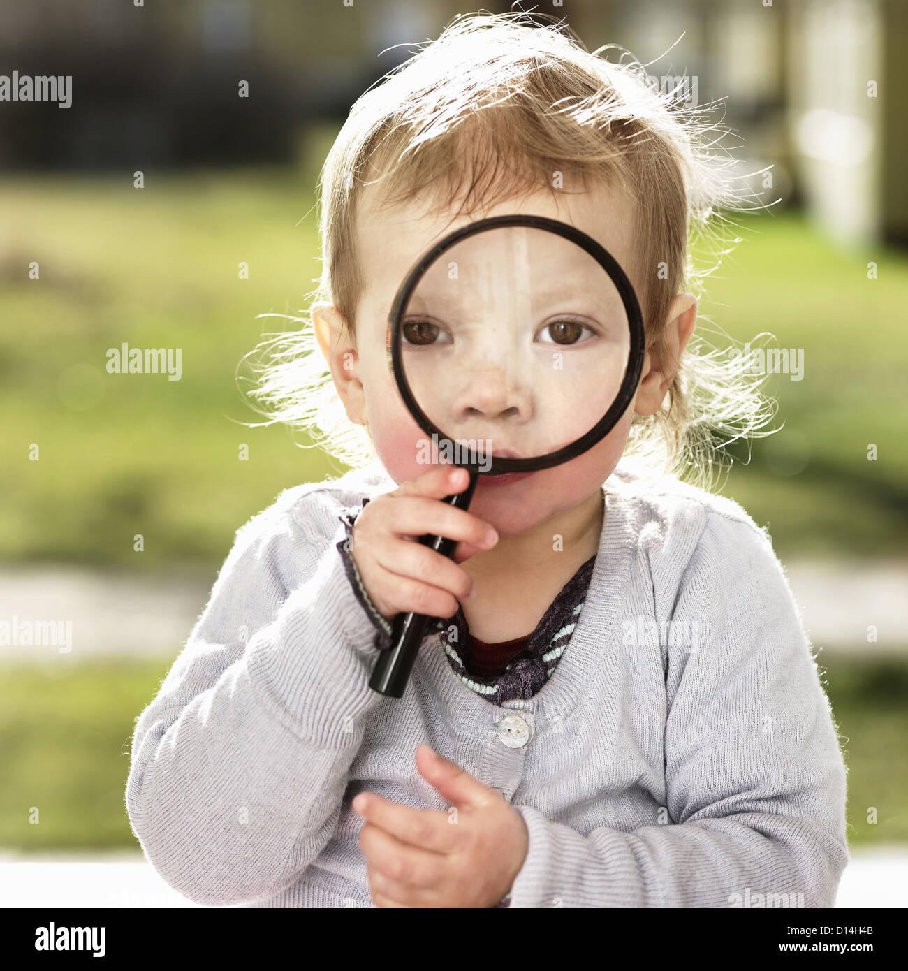 Toddler girl holding magnifying glass - Stock Image