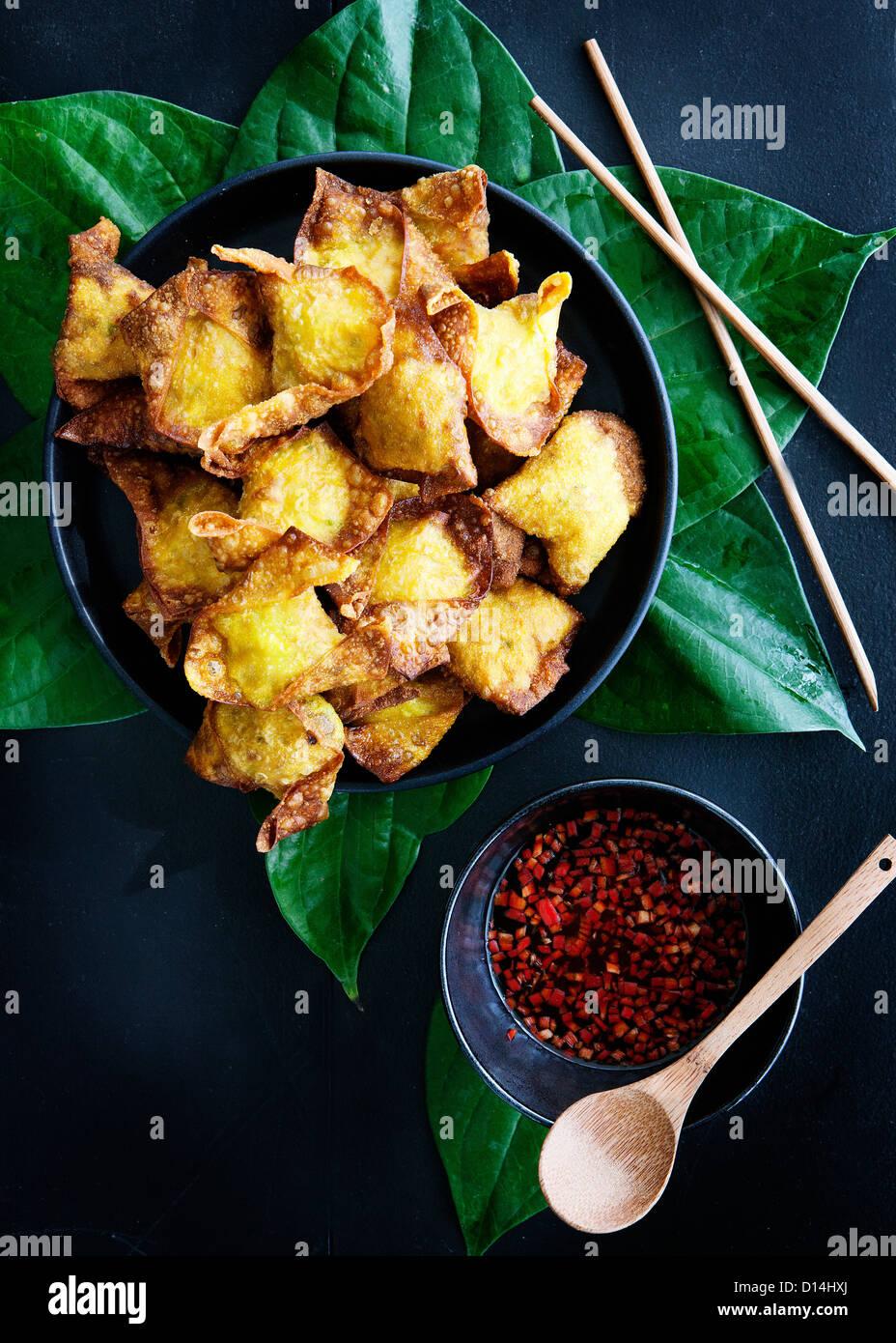 Plate of deep fried dumplings with sauce - Stock Image