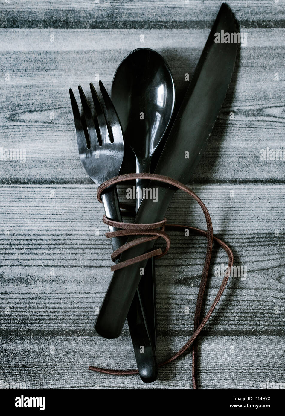 Wrapped cutlery on wooden table - Stock Image