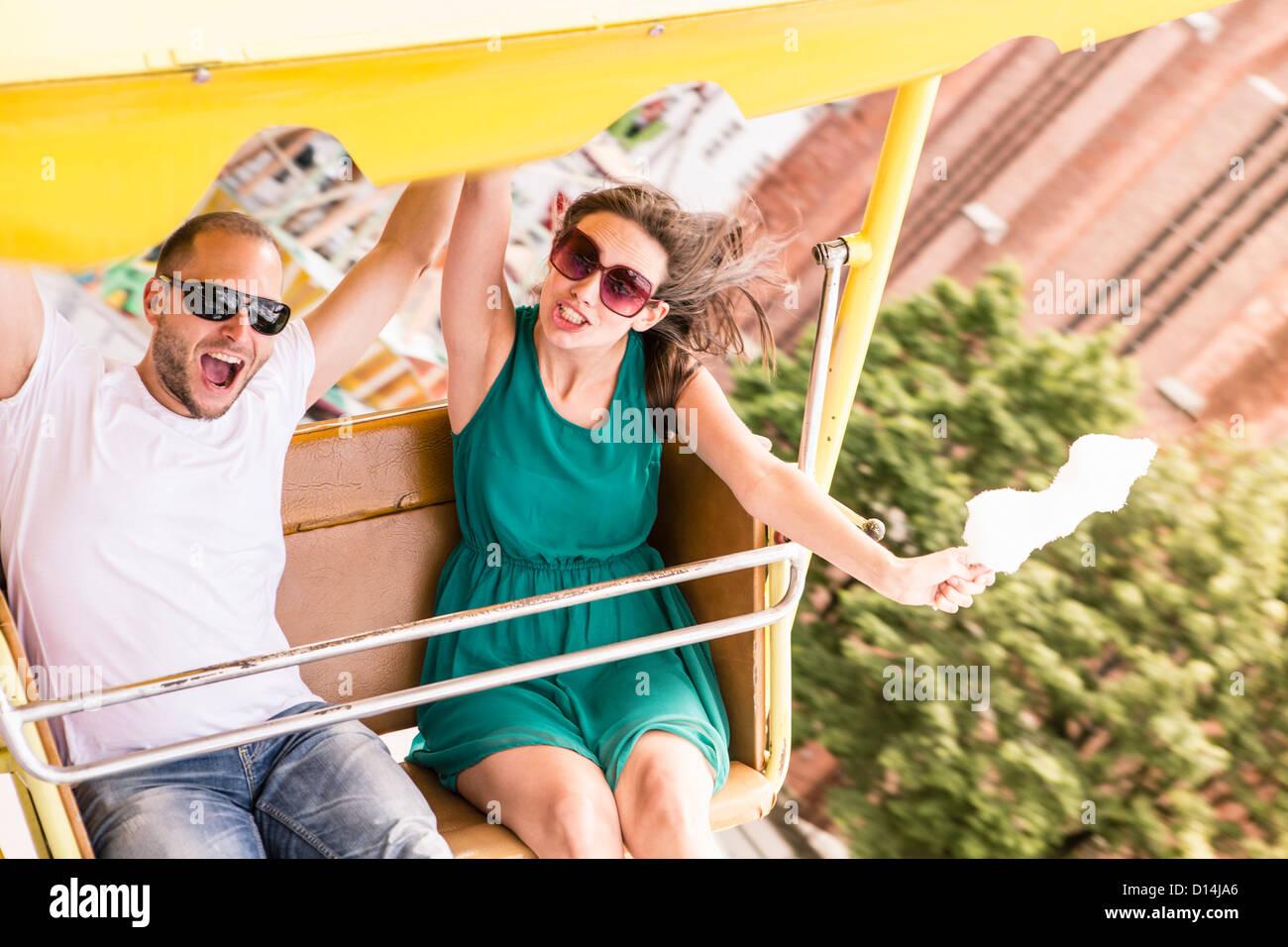 Couple riding amusement park ride - Stock Image