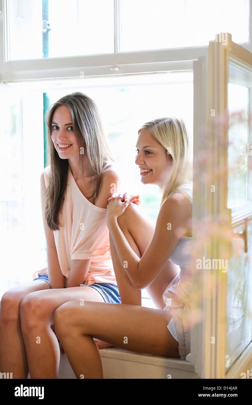 Smiling women sitting in windowsill - Stock Image