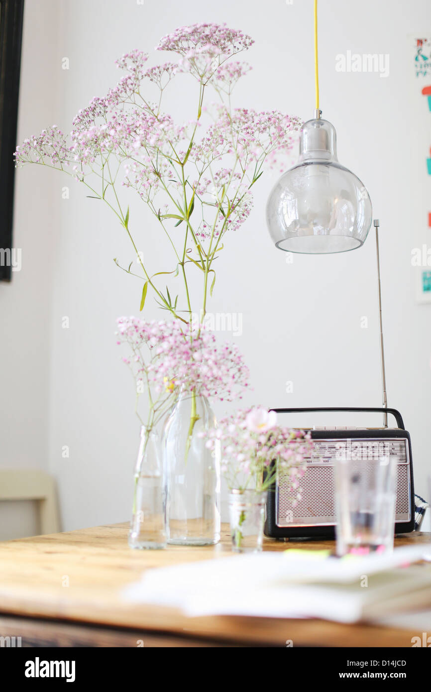 Flowers, radio and water glass on table Stock Photo