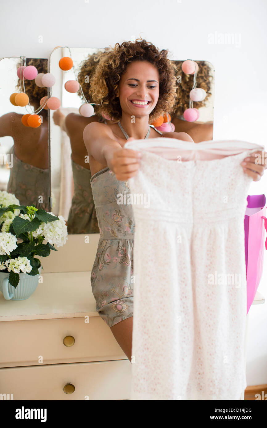 Smiling woman admiring new dress - Stock Image