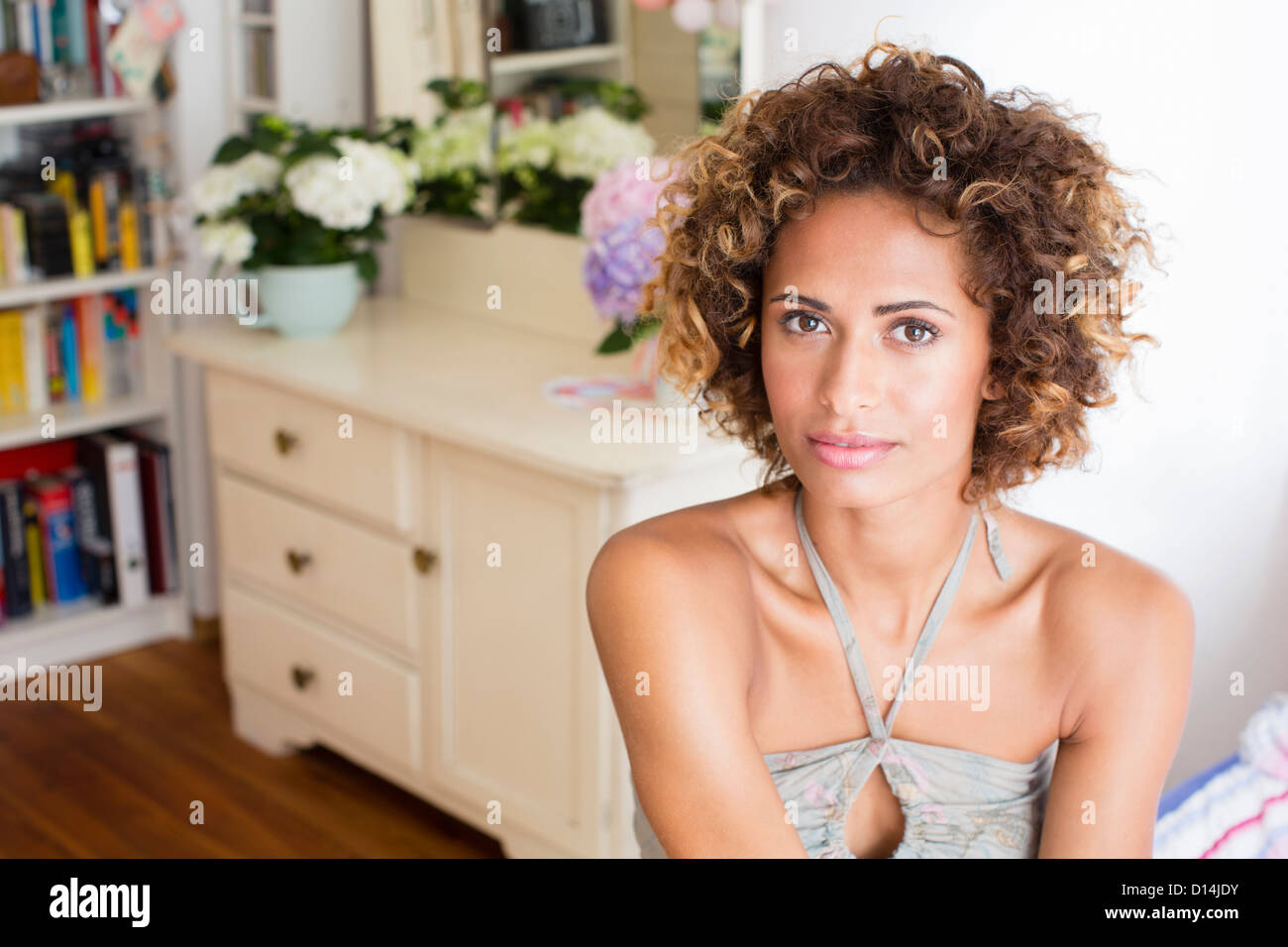 Woman sitting in bedroom - Stock Image