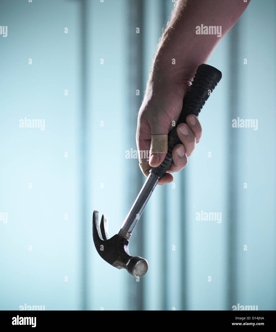 Close up of hand holding hammer - Stock Image