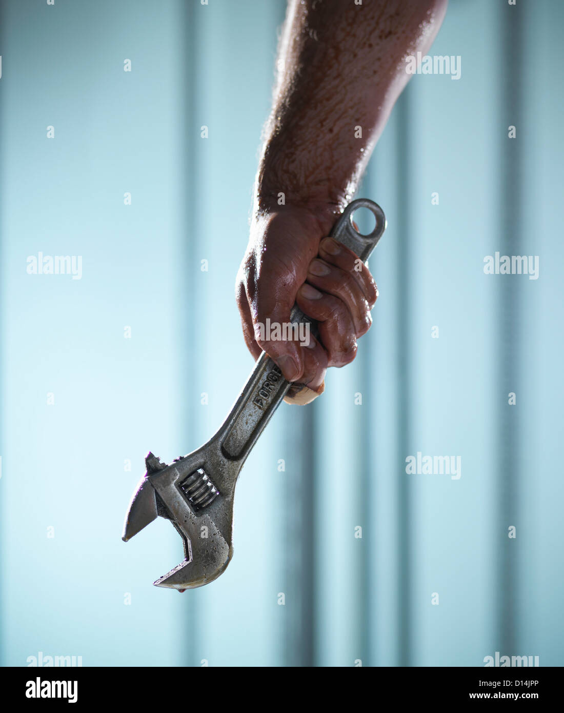Close up of hand holding wrench - Stock Image