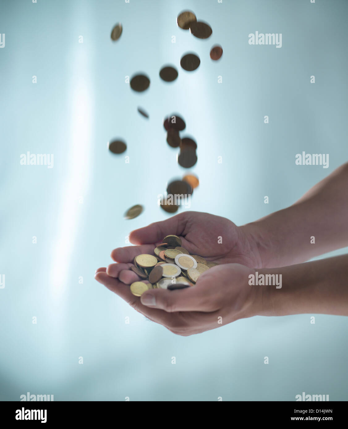 Close up of hands catching pile of coins - Stock Image