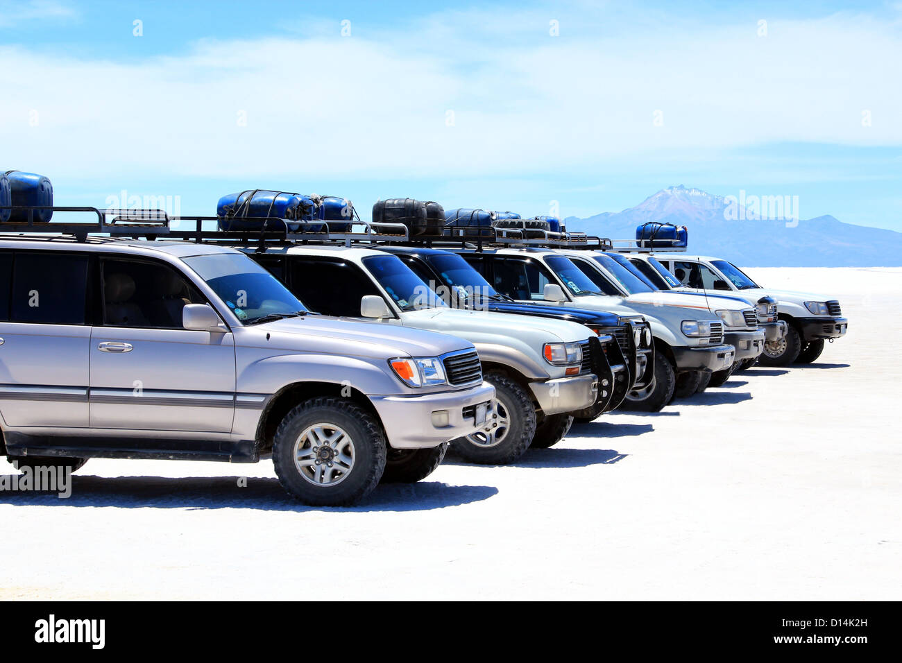 SUVs in a row in front of mountains Stock Photo