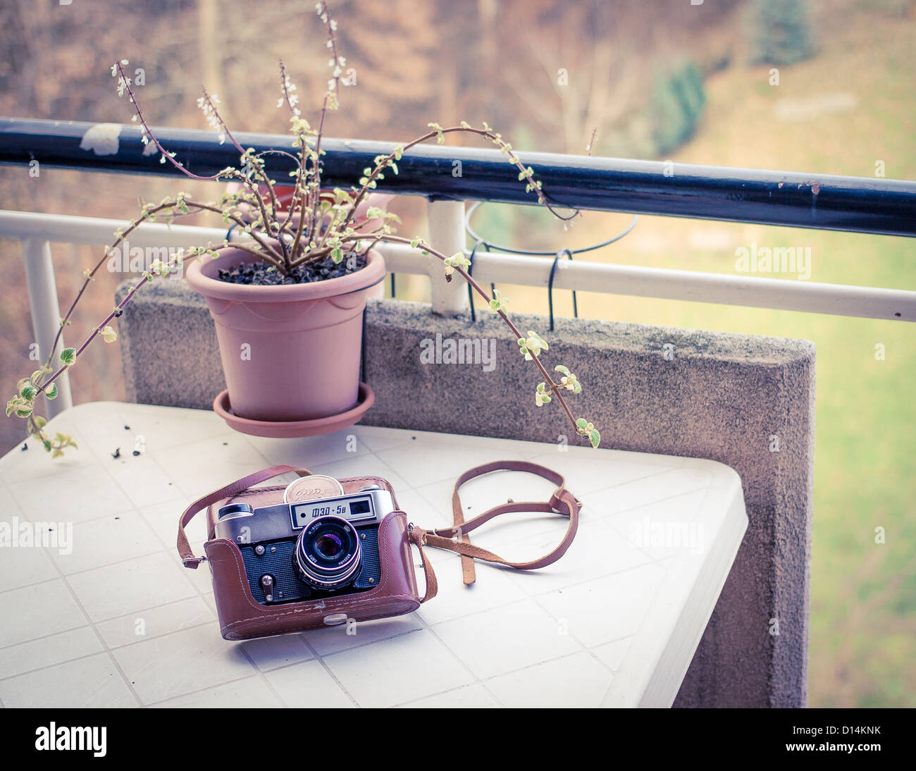 Vintage soviet analog camera (fed-5v) in its brown leather case, put on a white balcony table - Stock Image