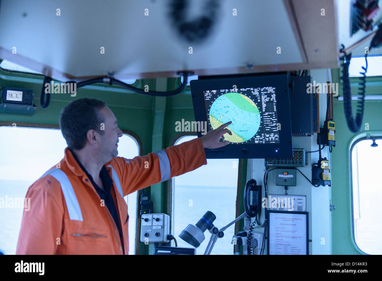 Tugboat worker examining map - Stock Image