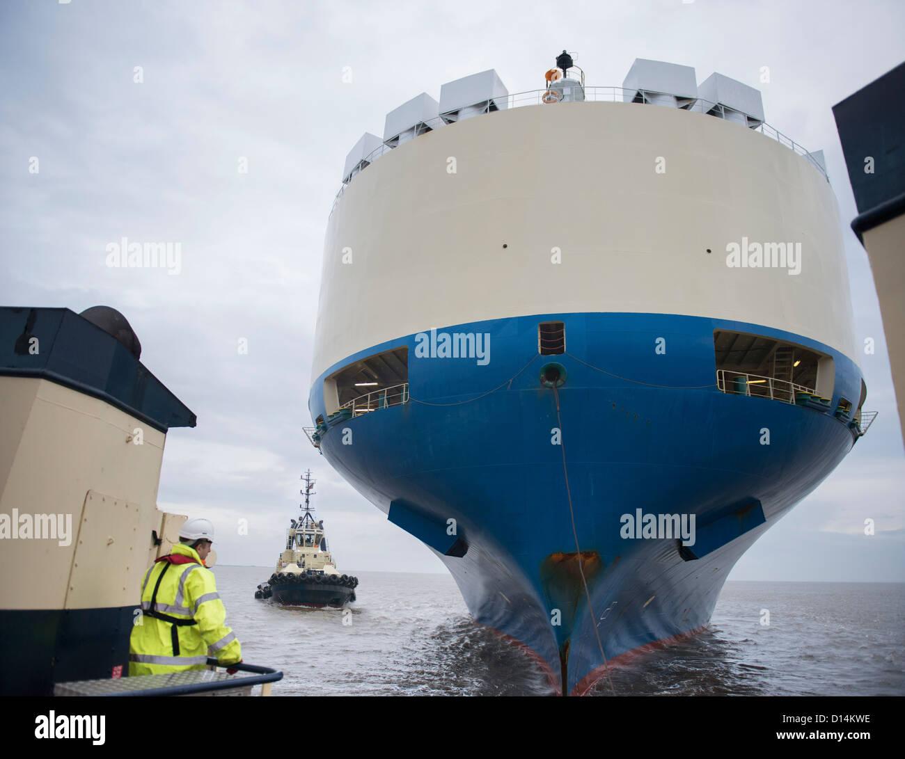 Tugboat sailing by large ship - Stock Image