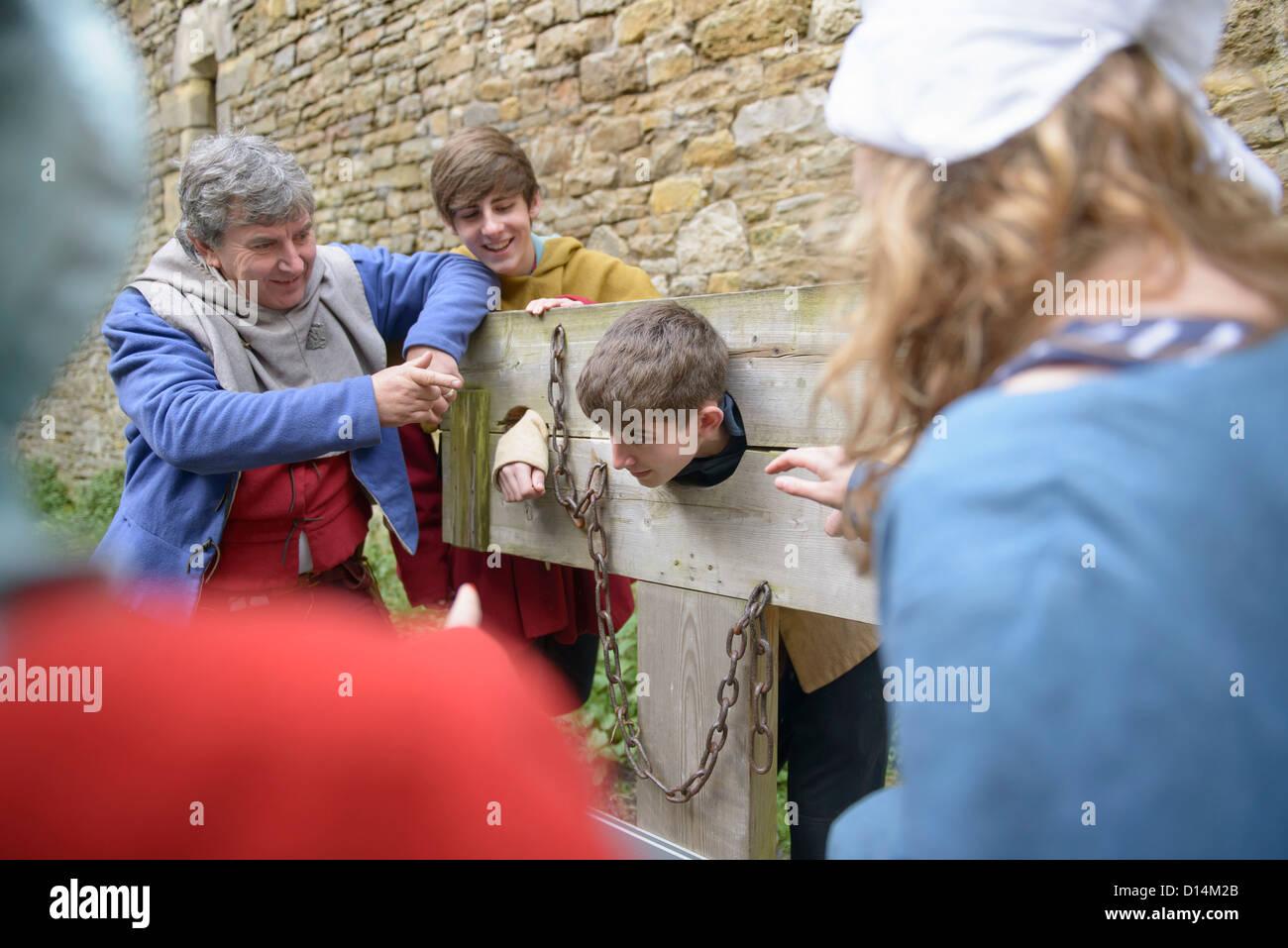 Students examining medieval stocks - Stock Image
