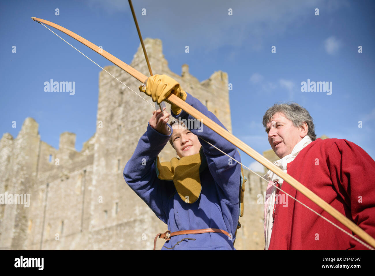 Student in period dress shooting arrow - Stock Image