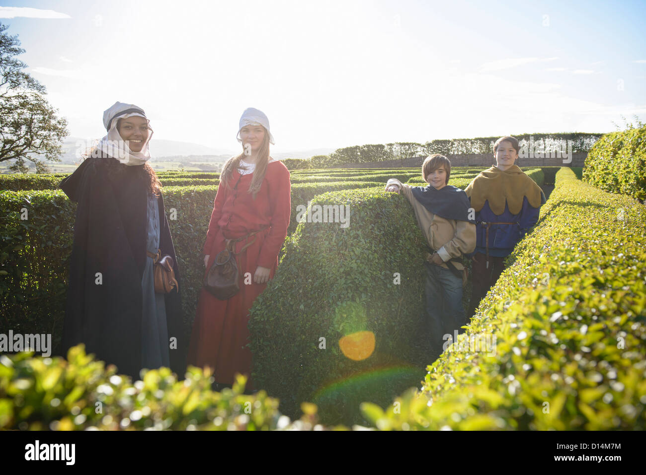 Students in period dress in hedge maze Stock Photo