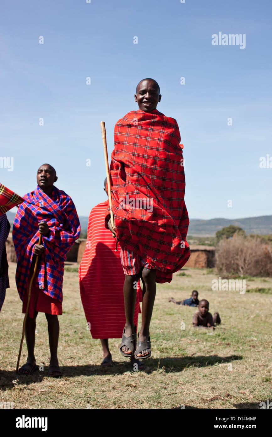 Maasai people walking in grassy field - Stock Image