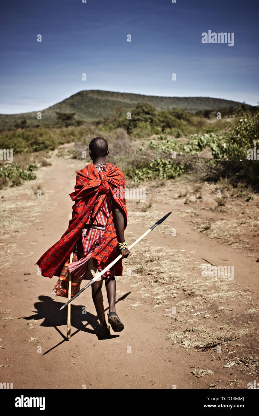 Maasai man walking on dirt road - Stock Image