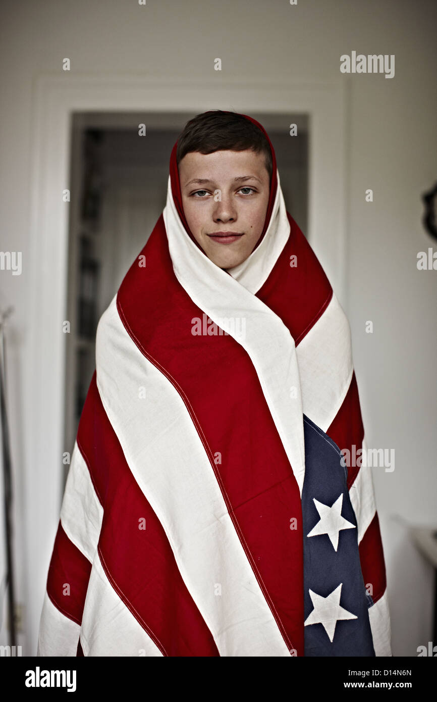 Boy wrapped in American flag indoors Stock Photo