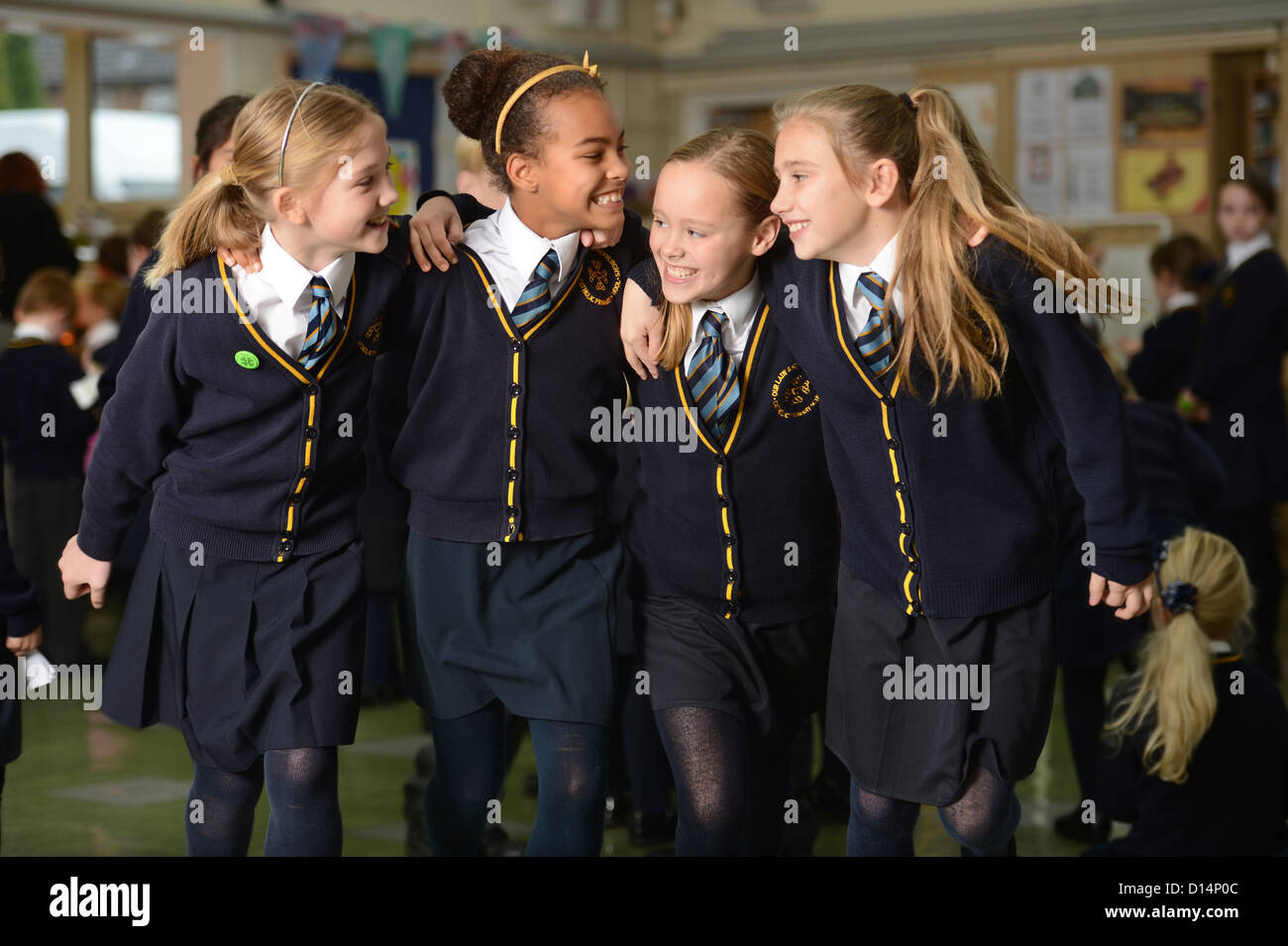 A group of friends leave morning assembly at Our Lady & St. Werburgh's Catholic Primary School in Newcastle - Stock Image