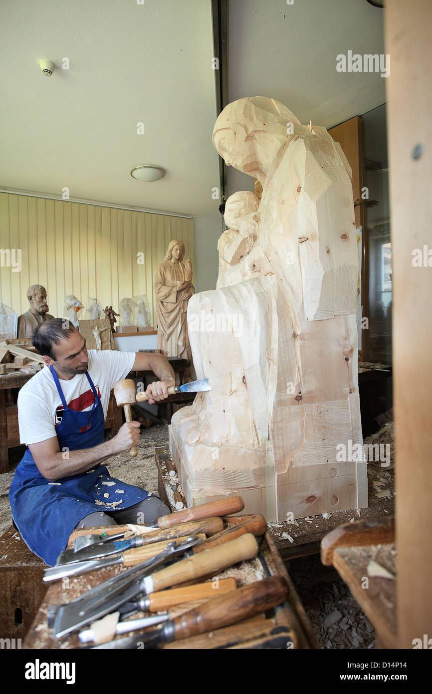 Sculptor chiseling figure from wood - Stock Image
