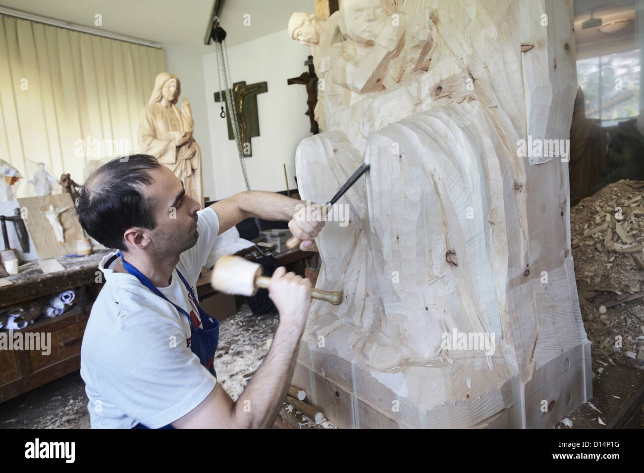 Sculptor chiseling figure from wood Stock Photo